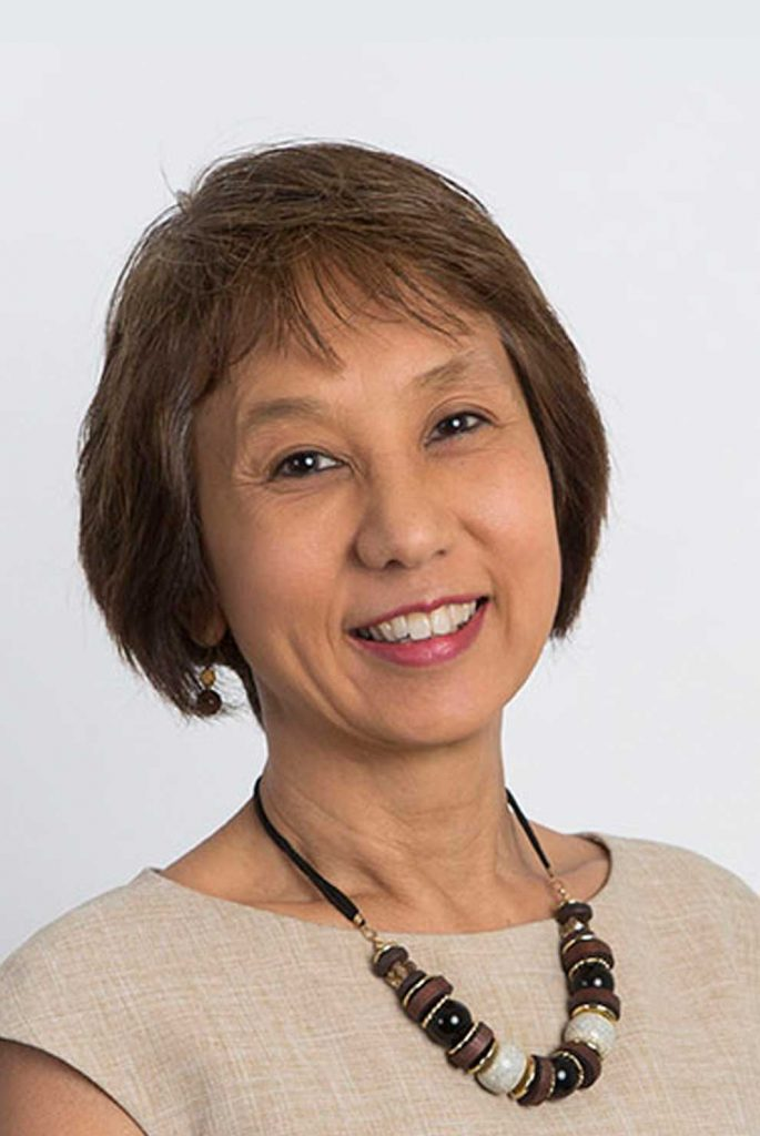 Bernadette Wright wearing an elegant beige top and a necklace with black, white and wooden pearls