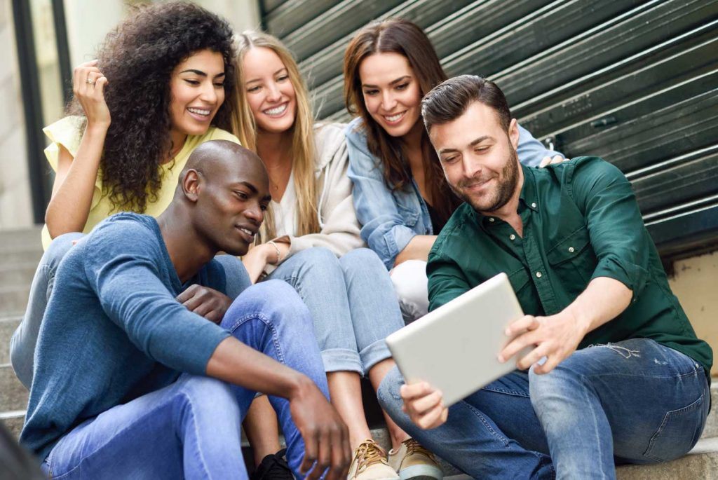 Five young people from diverse countries of origin sitting closely together looking at an electronic tablet