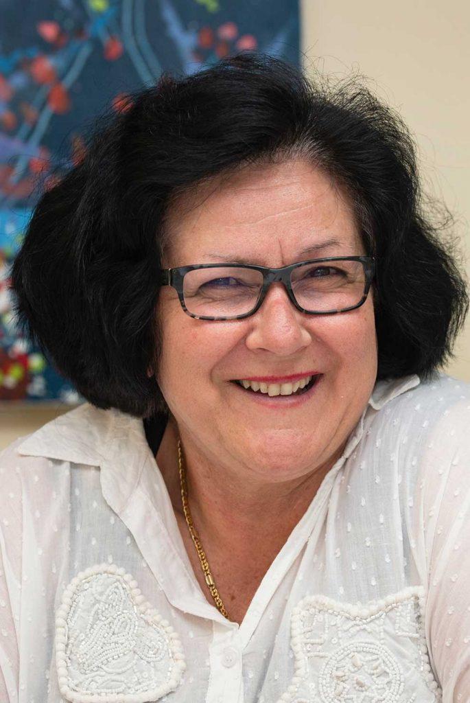 Melissa Del Borrello wearing square-shaped glasses and smiling