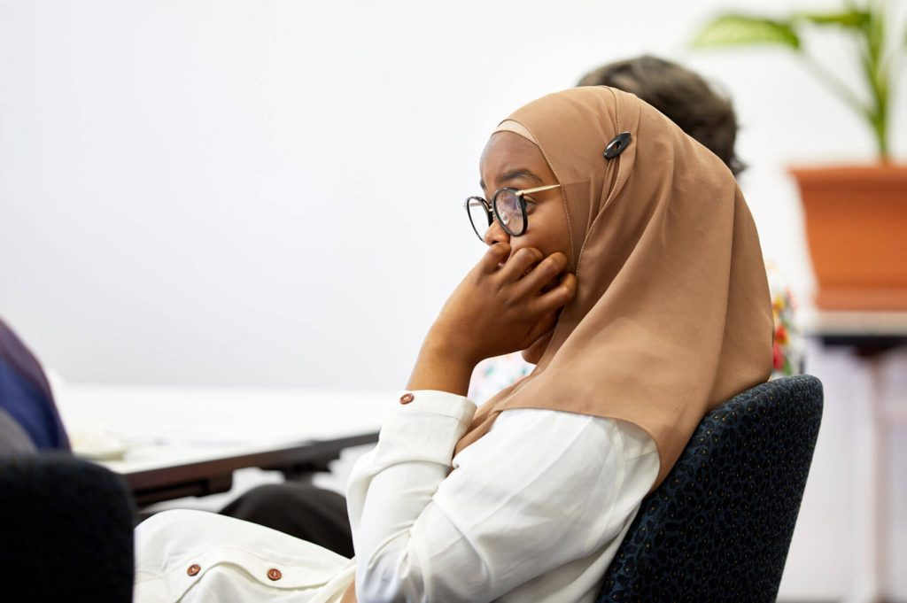 young migrant woman, sitting in a meeting room listening attentively