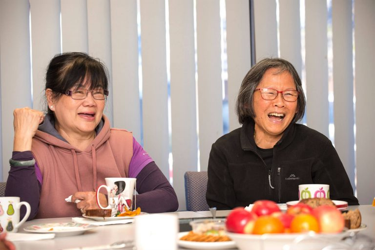 Two migrant women laughing whilst they enjoy morning tea
