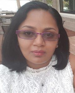 Asha Selathurai has kin-length black hair and is wearing purple-framed slightly tinted glasses