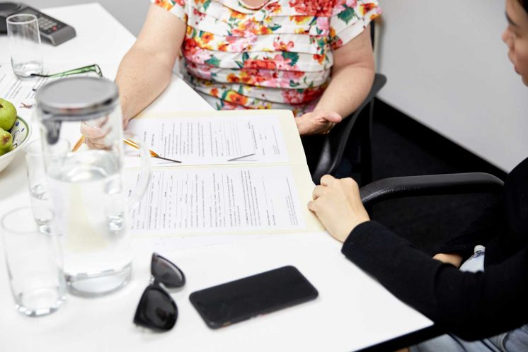 An advocate and a client sitting down and filling out forms
