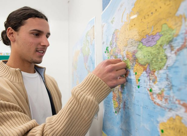 Young man putting a sticker on a specific location in a world map on the wall