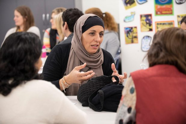 Migrant woman wearing a hijab and engaging in group discussion
