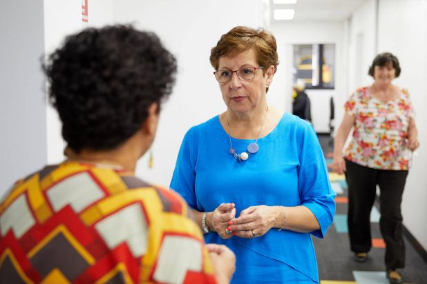 Kin Staff members engaging in conversation in the hallway of the office building