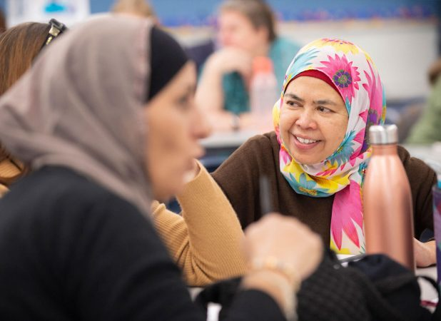 Training group session, with the focus on a migrant woman smiling and wearing a colourful hijab