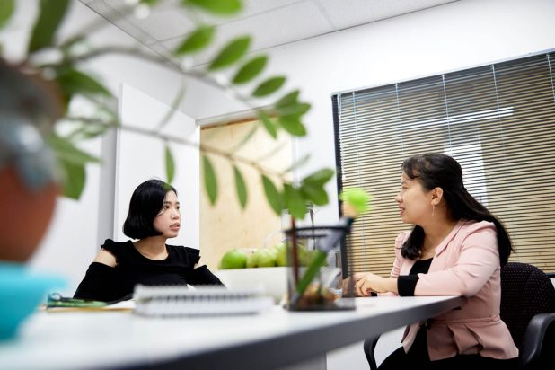 creative image of two women sitting around a table talking