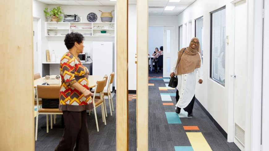 Kin premises in use. Woman on the left in the lunch room, young lady on the right coming down the hall way and a group of carers meeting in the back room